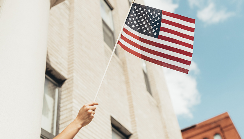 Person waving flag outside of window