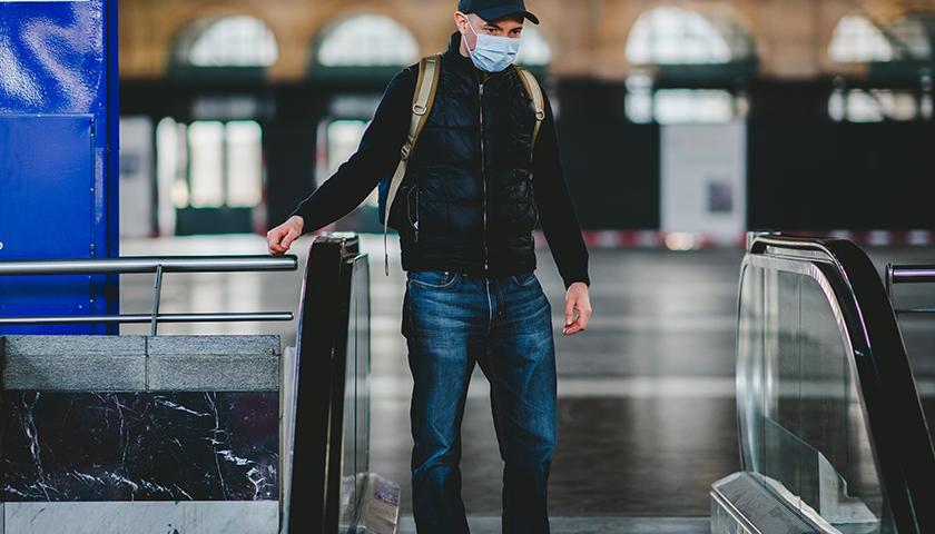 Man on escalator with mask on