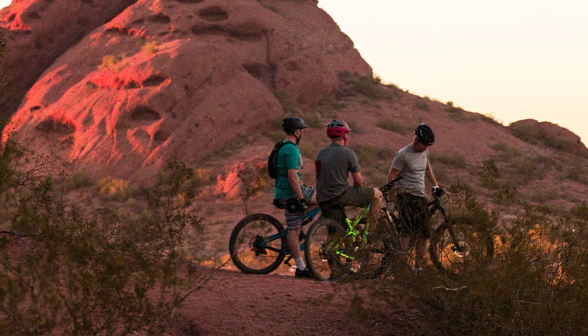 Three people on bikes in Arizona during sundown
