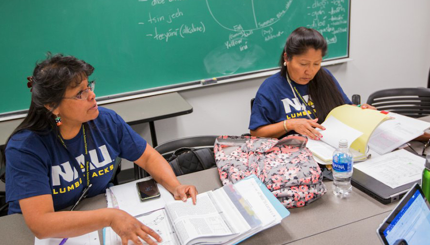 Photo of two teachers in a classroom going through papers.