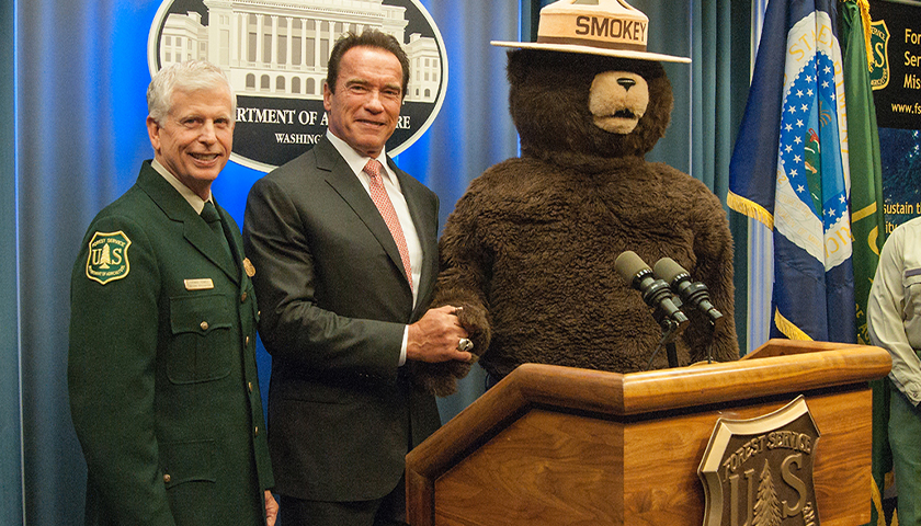 From left: U.S. Forest Service Chief Tom Tidwell, former California Governor Arnold Schwarzenegger and Smokey Bear pose during an event honoring Gov. Schwarzenegger as an honorary Forest Ranger at the U.S. Department of Agriculture in Washington, D.C. Wed., Oct. 29, 2013. Gov. Schwarzenegger is being honored for his signing and implementing the landmark California Global Warming Solutions Act of 2006 and continued leadership on climate change since leaving office. USDA photo by Bob Nichols