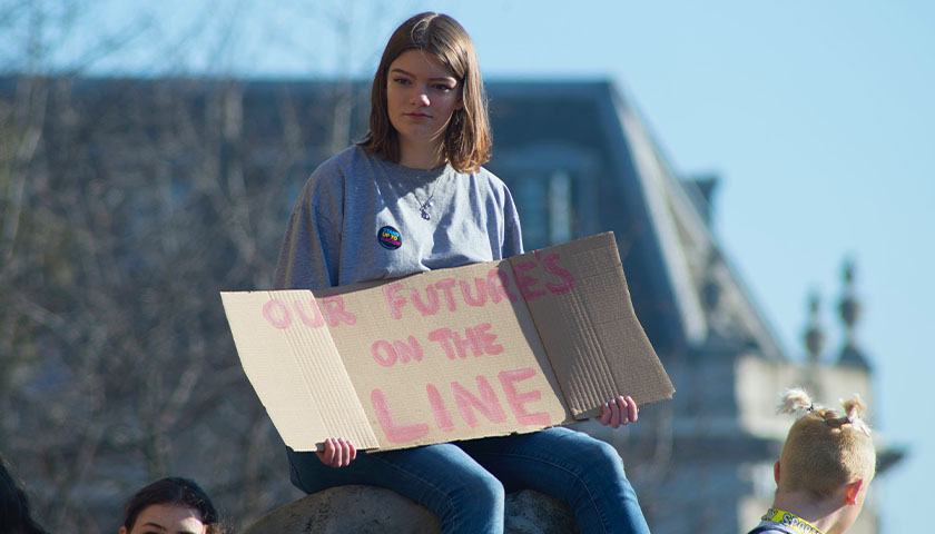 """Woman holding sign that says """"Our future's on the line"""""""